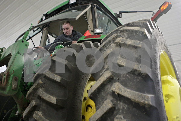 Rob Winner – rwinner@shawmedia.com<br /> <br /> Mike Schweitzer lowers a wire harness down from the cab of his tractor to later attach to his field sprayer while preparing for the upcoming planting season in Malta, Ill., Wednesday, March 27, 2013.