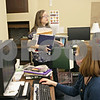 Rob Winner – rwinner@shawmedia.com<br /> <br /> Graphics design and public relations assistant Emily Gron (left) carries items from a dumb waiter to her new work station on the third floor as Jodi Sapita works at her desk at the DeKalb Public Library in DeKalb, Ill., Wednesday, March 20, 2013.