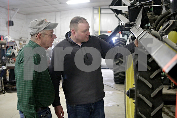 Rob Winner – rwinner@shawmedia.com<br /> <br /> Paul Schweitzer (left) and his son Mike Schweitzer look over a field sprayer while preparing for the upcoming planting season in Malta, Ill., Wednesday, March 27, 2013.