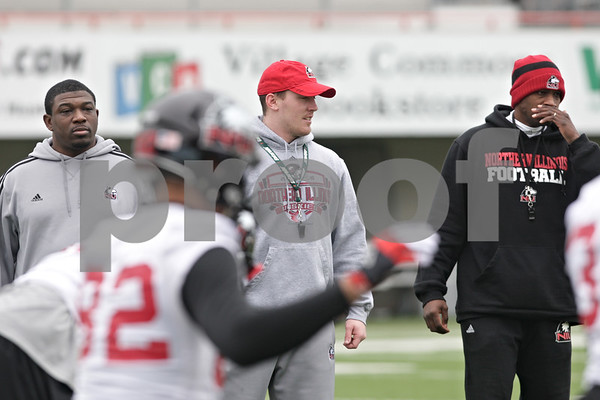 Rob Winner – rwinner@shawmedia.com<br /> <br /> Northern Illinois coaches Thad Ward (from left to right), Pat McAvoy and Kelton Copeland watch the team warmup during the start of practice at Huskie Stadium in DeKalb, Ill., Wednesday, March 27, 2013.