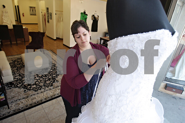 Rob Winner – rwinner@shawmedia.com<br /> <br /> Marissa Caltagerone, co-owner of Alexis Kay Design, Inc. in downtown DeKalb, adjusts the straps on a wedding dress on Thursday, March 21, 2013.