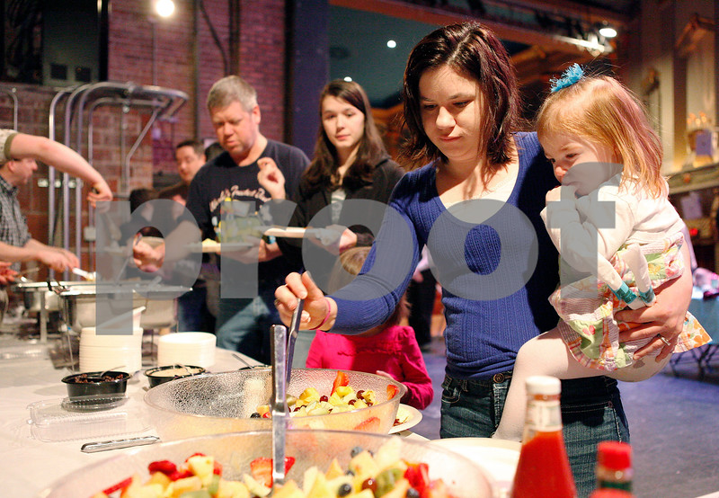 """Erik Anderson - For the Daily Chronicle <br /> DeKalb mother, Emily Miner, scoops out pieces of fruit for her daughter Charlotte, 2, during Breakfast with the Bunny at the Egyptian Theater in downtown DeKalb on Saturday, March 23, 2013. The event started with breakfast at 9 a.m. then the festivities until 10:30 a.m. and finally the showing of the movie, """"Hop"""" at 11 a.m."""