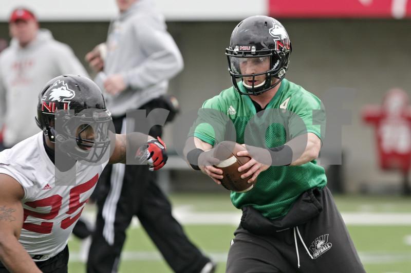 Rob Winner – rwinner@shawmedia.com<br /> <br /> Northern Illinois quarterback Jordan Lynch (center) fakes a handoff to Giorgio Bowers (left) during practice at Huskie Stadium in DeKalb, Ill., Wednesday, March 27, 2013.