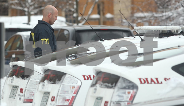 Kyle Bursaw — kbursaw@shawmedia.com<br /> <br /> A member of the FBI walks past NIU police vehicles. The FBI and Illinois State Police served a search warrant at the University Police and Public Safety building at Northern Illinois University in DeKalb, Ill. on Wednesday, March 6, 2013.