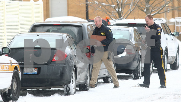 Kyle Bursaw — kbursaw@shawmedia.com<br /> <br /> An FBI official and NIU police official walk back to the University Police and Public Safety building. The FBI and Illinois State Police served a search warrant at the building at Northern Illinois University in DeKalb, Ill. on Wednesday, March 6, 2013.