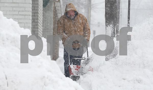 Kyle Bursaw — kbursaw@shawmedia.com<br /> <br /> William Walls, of Delano's Home Decorating, blows snow off of the sidewalk on North Fourth Street in DeKalb, Ill. on Tuesday, March 5, 2013.