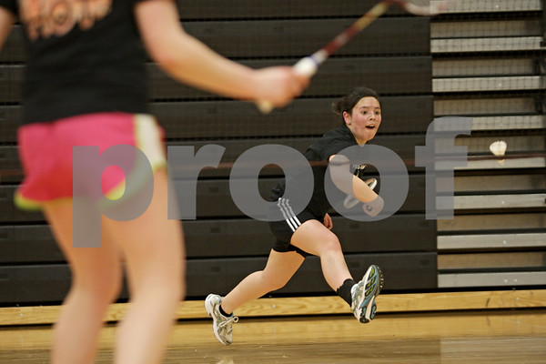 Rob Winner – rwinner@shawmedia.com<br /> <br /> Jaci Nguyen (right), a senior, runs after a shuttlecock during badminton practice with Tristan Draper (left), a junior, at DeKalb High School on Thursday, March 21, 2013.