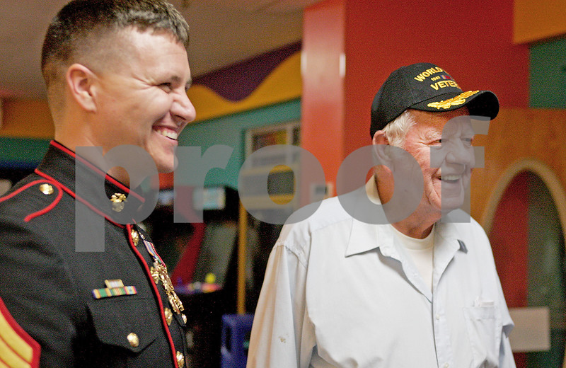 Monica Maschak - mmaschak@shawmedia.com<br /> Marine Staff Sergeant Chase Kovarik, of Maple Park, shares a laugh with World War II Marine veteran Don Mattson, 89, of Malta, at Mardi Gras Lanes in DeKalb on Tuesday, April 30, 2013. Mattson was attending an end-of-season banquet for his bowling league when Kovarik dropped in to surprise Mattson and thank him for his service with a hat and a patch.