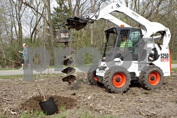 Rob Winner – rwinner@shawmedia.com<br /> <br /> DeKalb Park District worker Tom Boyce uses an auger attached to a Bobcat to drill new holes for shrubs to be planted along the DeKalb Nature Trail near Sycamore Road and Greenwood Acres Drive in DeKalb, Ill., Thursday, May 2, 2013.