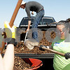 Monica Maschak - mmaschak@shawmedia.com<br /> Volunteer Zhizi Li, with Northern Illinois University's Alpha Phi Omega chapter, helps to move mulch from the bed of a truck to a wheel barrel to be spread around the site of a future garden outside of the DeKalb County Community Services Department on Saturday, April 27, 2013. The Community Services Department partnered with the DeKalb County Community Gardens to install a half-acre garden that will feature 30 raised beds of fruits, vegetables and herbs to increase fresh produce for low-income residents and those isolated from full-service grocery stores. The garden will initially serve the Women, Infants & Children program, Veterans Assistance Commission, residents at Heritage Woods and families enrolled in Head Start. The funding to start the garden came from $1,500 in federal grants.
