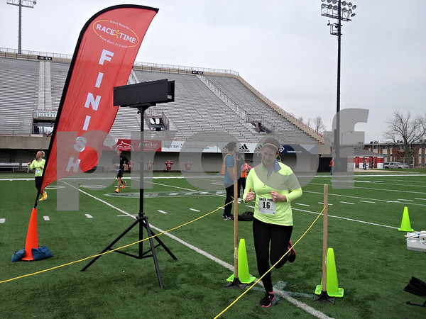 Stephanie Hickman - shickman@shawmedia.com <br /> <br /> Laura Caskey crosses the finish line at the Huskie Stadium 5K Race at Northern Illinois University Sunday. The race benefited NIU's Sports Management graduate program, Adventure Works in DeKalb and Share Your Soles in Chicago.