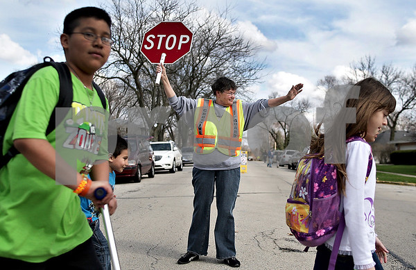 Monica Maschak - mmaschak@shawmedia.com<br /> Crossing Guard Charlotte Richards stops traffic to allow children leaving Jefferson Elementary School to cross the intersection of Ridge Drive and Huntington Road in DeKalb on Friday, April 26, 2013. Richards, who has been a crossing guard on this corner since January, received commendation from the DeKalb Police Department for her work when she protected kids from police cars that were speeding by.