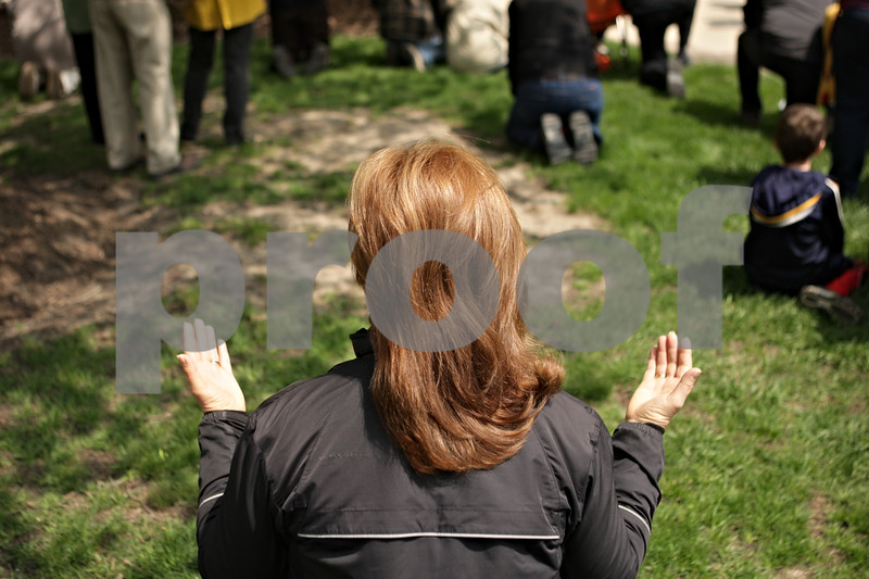 Rob Winner – rwinner@shawmedia.com<br /> <br /> DeKalb resident Kris Grant raises her hands while kneeling during the National Day of Prayer event outside the DeKalb County Courthouse in Sycamore, Ill., Thursday, May 2, 2013.