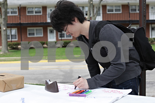 """Rob Winner – rwinner@shawmedia.com<br /> <br /> Northern Illinois University senior Yen Wei writes """"Pass tax class"""" on a sheet of paper for prayers during the #Prayers2Pass event outside St. Paul's Episcopal Church in DeKalb, Ill., Tuesday, April 30, 2013. The event offered passersby snacks, drinks and prayers to those who wanted them."""
