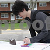 "Rob Winner – rwinner@shawmedia.com<br /> <br /> Northern Illinois University senior Yen Wei writes ""Pass tax class"" on a sheet of paper for prayers during the #Prayers2Pass event outside St. Paul's Episcopal Church in DeKalb, Ill., Tuesday, April 30, 2013. The event offered passersby snacks, drinks and prayers to those who wanted them."