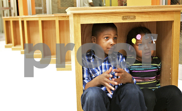 Monica Maschak - mmaschak@shawmedia.com<br /> Da Von Grant, 5, and sister Jordan Grant, 3, from Two Rivers Head Start, sit comfortably in their new bookcase during the DeKalb-Sycamore Bookcase Project's second annual awards ceremony at Huntely Middle School on Saturday, May 4, 2013. Fifty-two children received starter libraries and bookcases. Volunteer craftsmen built the bookcases, and art students painted literary themes on tote bags to hold the books, which were donated by community members.
