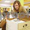 Monica Maschak - mmaschak@shawmedia.com<br /> Lissa Thompson and her son Jackson Brovelli, 4, peek into a box of 55 books for his starter library and bookcase at the DeKalb-Sycamore Bookcase Project's second annual awards ceremony at Huntley Middle School on Saturday, May 4, 2013. More than 4000 books were donated during a six-week period in March and April. Volunteer craftsmen built the bookcases, and art students painted literary themes on tote bags to hold the books.