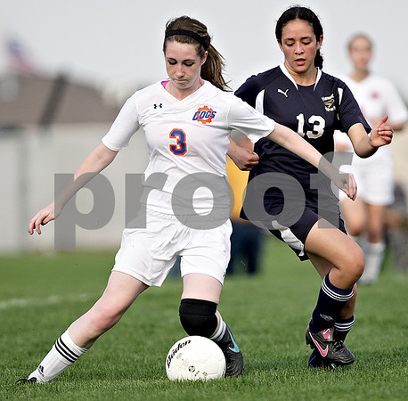 Monica Maschak - mmaschak@shawmedia.com<br /> Alanna Wilcox (3) feels pressure from Lirio Rubio (13) to kick the ball during the Class 1A Genoa-Kingston Regional semifinal game on Wednesday, May 8, 2013. The Cogs beat Hiawatha 4-1.