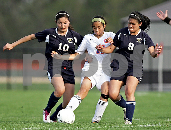 Monica Maschak - mmaschak@shawmedia.com<br /> Nicole Hebel (center) finds the ball between Hiawatha players Yulissa Solis (10) and Abi Garcia (9) in Class 1A Genoa-Kingston Regional semifinal game on Wednesday, May 8, 2013. The Cogs beat Hiawatha 4-1.
