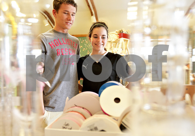 Monica Maschak - mmaschak@shawmedia.com<br /> Conner Hill, a junior at DeKalb, and his date Kelly Brown, a junior at Sycamore, decide on corsage and boutonniere items at Kar-Fre Flowers in Sycamore on Saturday, May 4, 2013. Hill and Brown plan to attend DeKalb's prom on the 11th and Sycamore's prom on the 18th, both at Northern Illinois University. The flower shop has made boutonniere and corsage arrangements for about eight high schools this prom season.