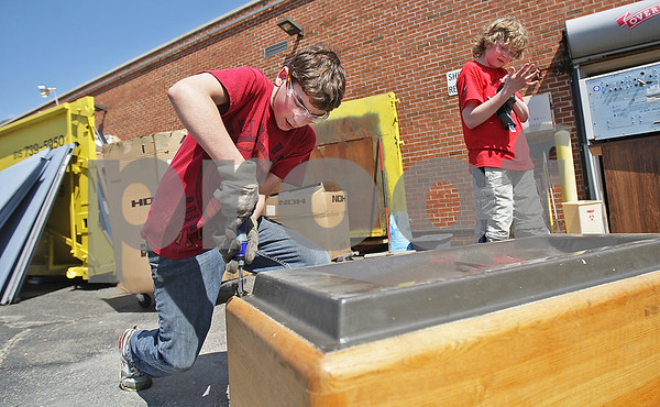 Monica Maschak - mmaschak@shawmedia.com<br /> Daniel Yonke (left), 13, friend of Timothy McMahon, 12, takes furniture apart before putting it in the dumpster behind them outside of the old Dekalb Clinic on Wednesday, May 1, 2013. The building, which has been vacant since 2009, was auctioned last month and purchased by Timothy's father, Bill McMahon, in the last couple weeks. McMahon has plans to turn the building into a banquet hall. His two sons and their friends helped with cleaning out the building from furniture and other items left behind by the clinic four years ago.