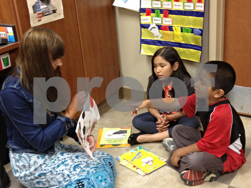 Stephanie Hickman - shickman@shawmedia.com<br /> <br /> First-grader Jonik Jaimes points to a picture as Rachel Petersen reads to him and his classmate, Sophia Ruvalcaba at Cortland Elementary School Friday. Petersen, a senior at DeKalb High School, came with her Spanish class to visit the elementary students.