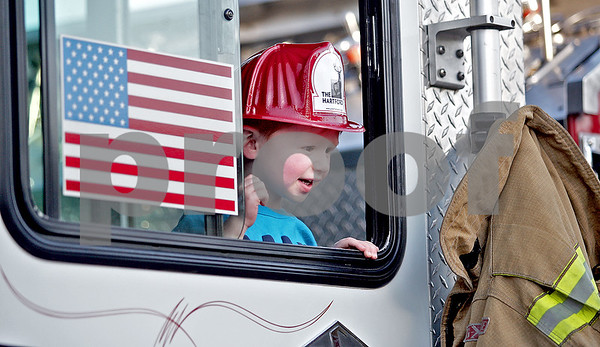 Monica Maschak - mmaschak@shawmedia.com<br /> Noah Dean, 2, of Sycamore, peeks out of a fire truck window at a Touch-A-Truck event hosted by Discover Sycamore on Tuesday, May 14, 2013.  The event allowed children to become familiar with vehicles belonging to the police department, fire department, EMS and Public Works.