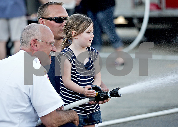 Monica Maschak - mmaschak@shawmedia.com<br /> Sycamore Fire Chief Pete Polarek (left) shows Kylie Runkle, 3, and her dad, Brett Runkle, how to use a fire hose at a Touch-A-Truck event hosted by Discover Sycamore on Tuesday, May 14, 2013.  The event allowed children to become familiar with vehicles belonging to the police department, fire department, EMS and Public Works.