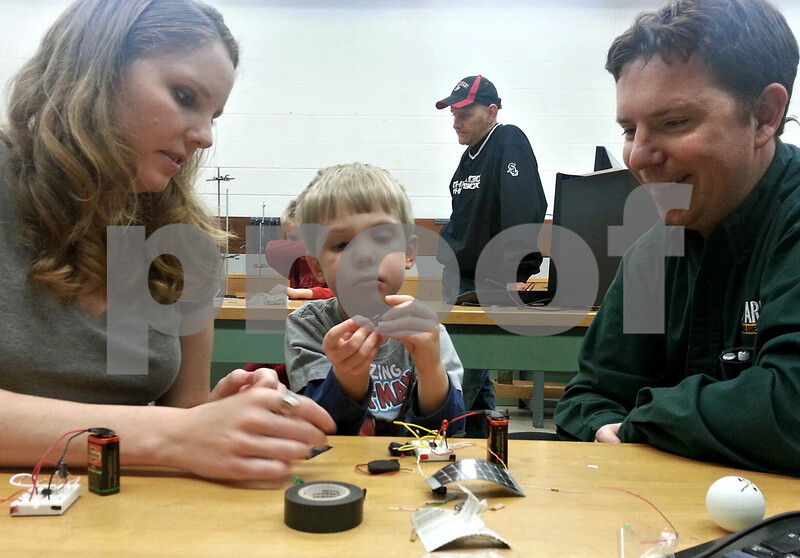 Felix Sarver – fsarver@shawmedia.com<br /> <br /> DeKalb residents Lena, 28, David, 33, and their son Jack, 4, work on building a circuit-based device in the Bright Futures Electric Art Lab on Saturday at Faraday Hall, Northern Illinois University. Bright Futures is a community program provided by NIU's STEM Outreach. The program helps people understand how electronics and electricity works through fun activities.