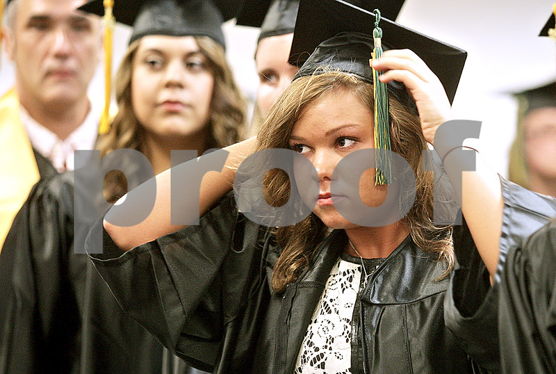 Monica Maschak - mmaschak@shawmedia.com<br /> Denise McDermott put on her cap and gown as she stands in alphabetical order among her peers during the 2:00 p.m. graduation at Kishwaukee College on Saturday, May 18, 2013. McDermott earned her Associates in Science.
