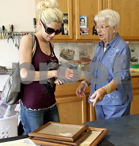 Monica Maschak - mmaschak@shawmedia.com<br /> Leah Stanton, of Malta, buys a few picture frames from Edna Carter during the annual community garage sale at The Bridges of Rivermist in DeKalb on Friday, May 17, 2013. Carter used this opportunity to have a moving sale.