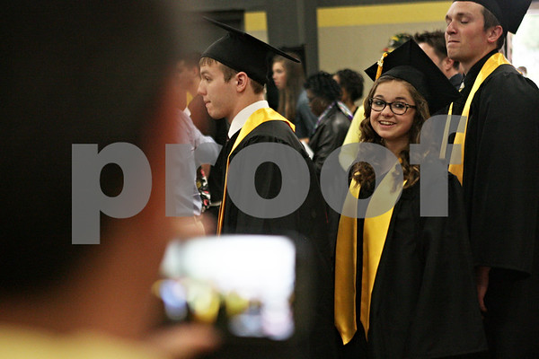 Rob Winner – rwinner@shawmedia.com<br /> <br /> McKenzie Palm looks to a group of parents and family members taking photographs and video of the 2013 graduating class of Sycamore High School as they enter the field house before their ceremony.