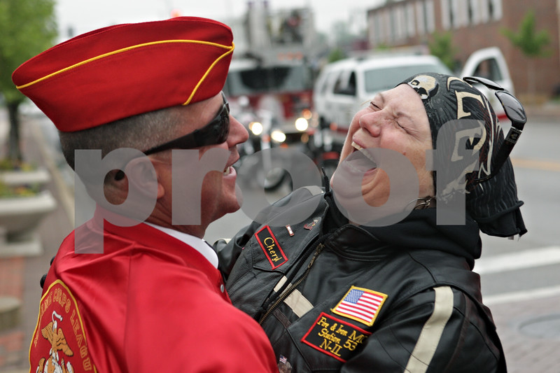 Rob Winner – rwinner@shawmedia.com<br /> <br /> Marine Corps veteran Mike Fogelsanger (left) is hugged by friend Cheryl Bush before the start of the Memorial Day parade in downtown DeKalb, Ill. Fogelsanger and Bush know each other through the Warriors' Watch Riders group.<br /> <br /> Monday, May 27, 2013