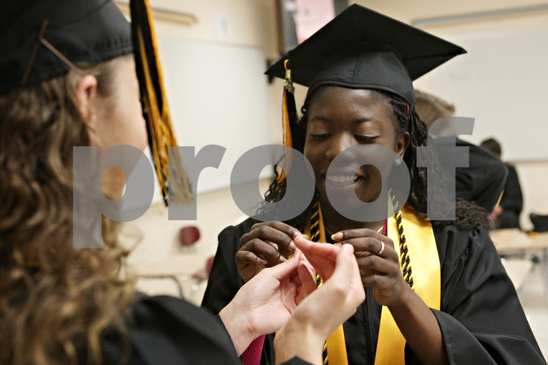 Rob Winner – rwinner@shawmedia.com<br /> <br /> Shekinah Bergmann (left) hands a bobby pin to classmate Grace Anati as the two prepare themselves before their commencement at Sycamore High School on Sunday, May 26, 2013.