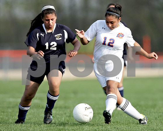 Monica Maschak - mmaschak@shawmedia.com<br /> Jasmine Ascencio, for Hiawatha, and Viviana Beltran, for Genoa-Kingston, race for the ball in the Class 1A Genoa-Kingston Regional semifinal game on Wednesday, May 8, 2013. The Cogs beat Hiawatha 4-1.