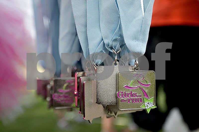 Monica Maschak - mmaschak@shawmedia.com<br /> All runners crossing the finish line received a medal in the area's first Girls on the Run 5K race at Hopkins Park in DeKalb on Saturday, May 18, 2013.