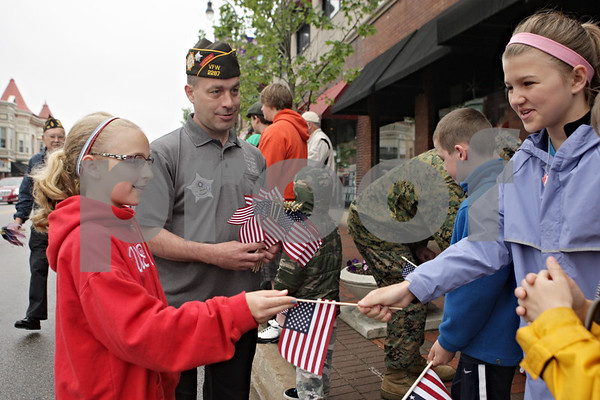 Rob Winner – rwinner@shawmedia.com<br /> <br /> Marcy Cliffe (left), 10, and her father, Rick Cliffe, the current Post Commander of VFW #2287, hand out flags to supporters of Monday's Memorial Day parade in downtown DeKalb, Ill.<br /> <br /> Monday, May 27, 2013
