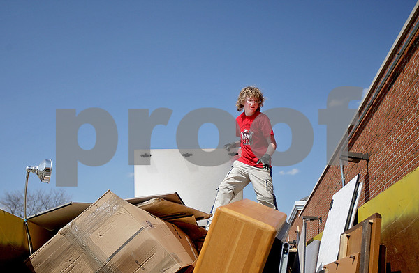Monica Maschak - mmaschak@shawmedia.com<br /> <br /> Timothy McMahon, 12, stands on top of a dumpster full of furniture and other miscellaneous items that was left in the old Dekalb Clinic, which has been vacant since 2009. The building was auctioned off last month and purchased by Timothy's father, Bill McMahon, within the last couple weeks. McMahon has plans to turn the building into a banquet hall.