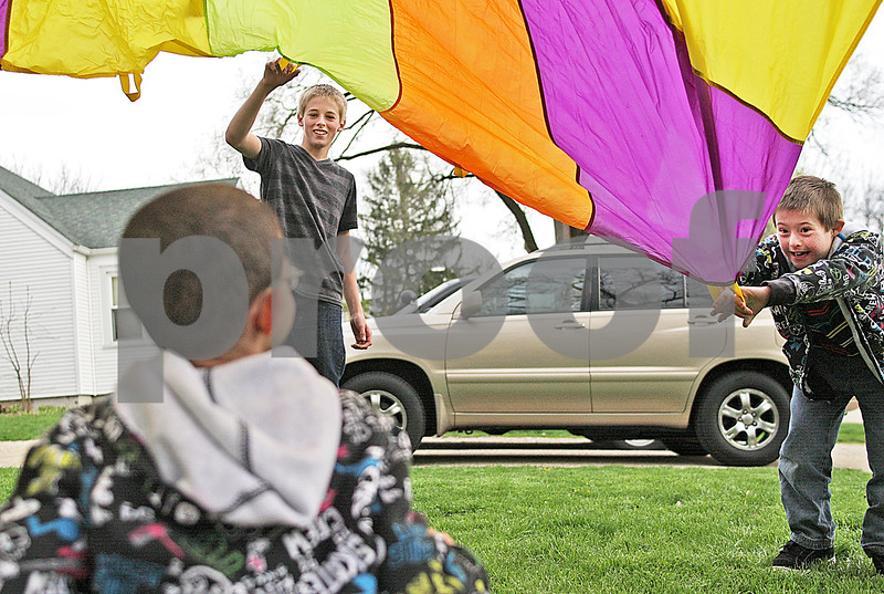 Monica Maschak - mmaschak@shawmedia.com<br /> Alex Scott, 14, and David Scott, 8, play parachute with their foster brother, who can not be named,  in the front yard of their adopted family's home in DeKalb on Friday, May 3, 2013. Roger and Marcia Scott have fostered more than 40 children since 1985. Of those children, the Scotts have adopted five.