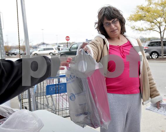 Monica Maschak - mmaschak@shawmedia.com<br /> Rene Polz donates a toy to the Toys For Tots drive at the DeKalb Walmart on Saturday, November 2, 2013.