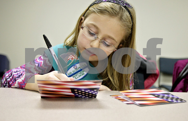 Monica Maschak - mmaschak@shawmedia.com<br /> Ella Follman, 9, of Girl Scout Troop 1620, writes thank you cards to veterans in DeKalb County at the Resource Bank in Genoa on Thursday, November 7, 2013.