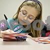 Monica Maschak - mmaschak@shawmedia.com<br /> Ella Follman, 9, of Girl Scout Troop 1620, writes thank you cards to veterans in DeKalb County at the Resource Bank in Genoa on Thursday, November 7, 2013.