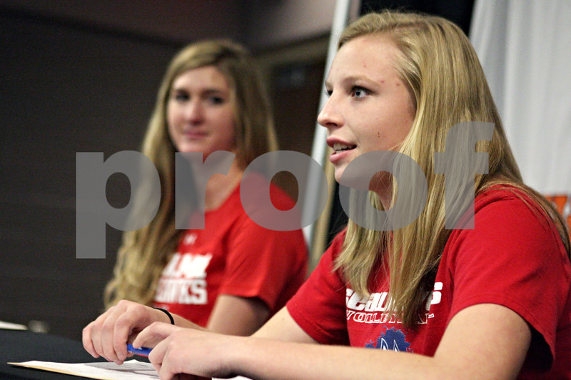 Rob Winner – rwinner@shawmedia.com<br /> <br /> Courtney Bemis (left) listens as Abby Hickey thanks her supporters after they both signed their letters of intent at Dekalb High School on Friday, Nov. 15, 2013. Bemis will be attending Miami of Ohio and Hickey will be attending Stony Brook University.