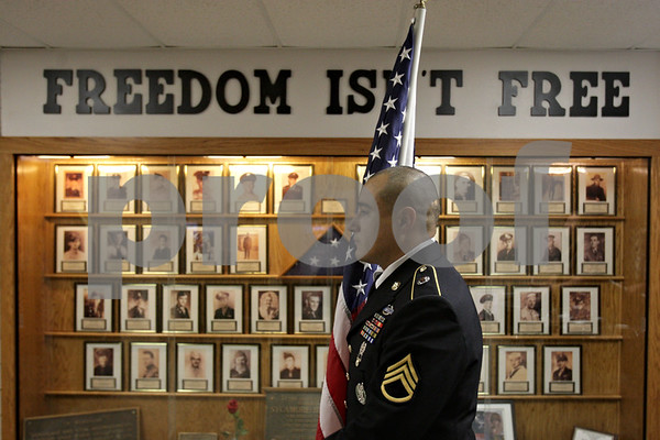 Rob Winner – rwinner@shawmedia.com<br /> <br /> Robert Martinez pauses in front of a display case honoring local veterans during a Veterans Day observance at Sycamore High School on Monday morning. Martinez has been serving in the Army since 2001.