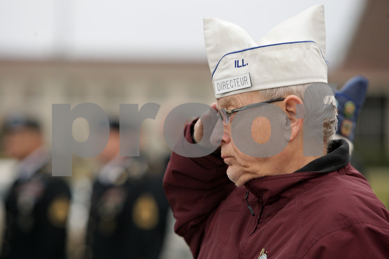 """Rob Winner – rwinner@shawmedia.com<br /> <br /> Frank Beierlotzer salutes as students from Sycamore High School sing """"The Star-Spangled Banner"""" during a Veterans Day observance outside the school on Monday, Nov. 11, 2013."""
