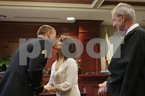 Rob Winner – rwinner@shawmedia.com<br /> <br /> Judge Thomas L. Doherty (right) watches as Steven Estes of DeKalb kisses his bride Annie Baccetti of Sandwich after the two were married at the DeKalb County Courthouse in Sycamore, Ill., Friday, Nov. 15, 2013. Estes is an Army Fire Support Specialist and will be deployed to Afghanistan in December.