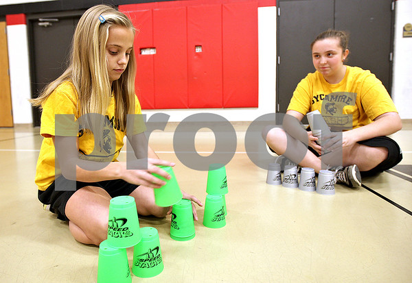 Monica Maschak - mmaschak@shawmedia.com<br /> Seventh graders Madison Hickey (left) and Madyson Hash stack cups during their gym class at Sycamore Middle School on Thursday, November 14, 2013. Students from the school hope to set a Guinness World Record during the Stack Up! cup-stacking event as part of Guinness World Records Day.