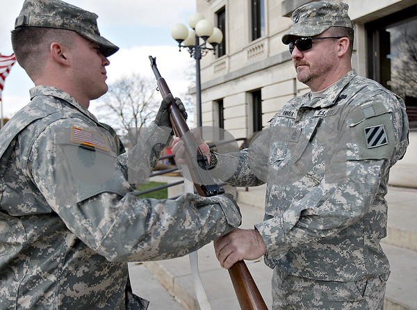 Monica Maschak - mmaschak@shawmedia.com<br /> Sgt. Sean Griffin (left) receives a rifle from Sgt. 1st Class Mike Emmer as Emmer's shift ends and Griffin's shift begins in front of the DeKalb County Court House on Saturday, November 9, 2013. Veterans took turns keeping vigil from 6 p.m. Friday to 6 p.m. Saturday.