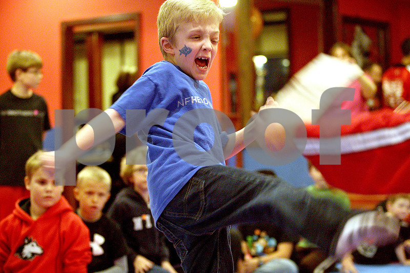 Monica Maschak - mmaschak@shawmedia.com<br /> Tyler Neppl, 8, breaks a wooden board with a kick at Billy Cho's United Tae Kwon Do Center for a Break-a-thon to benefit Neppl on Friday, November 15, 2013. Neppl has a rare genetic disorder called neurofibromatosis. His classmates, neighbors and friends came out to break boards at the Tae Kwon Do center where he is an orange belt.