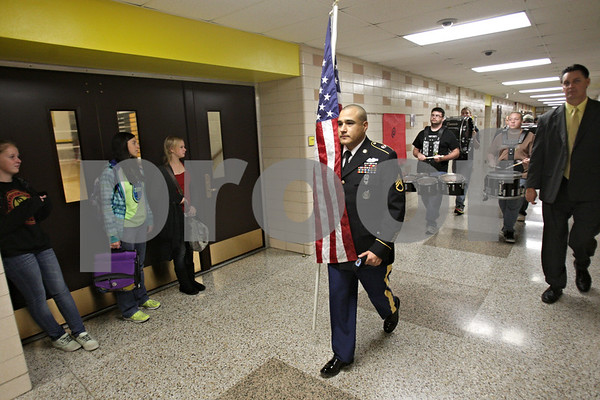 Rob Winner – rwinner@shawmedia.com<br /> <br /> Robert Martinez carries the flag while marching through a hallway at Sycamore High School for an observance of Veterans Day on Monday morning. Martinez has been serving in the Army since 2001.